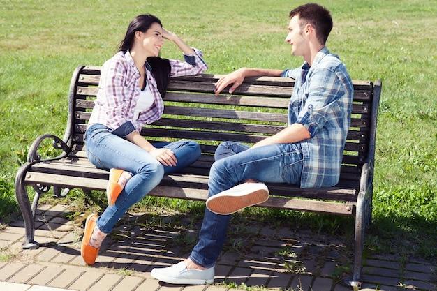 公園のベンチで休んで座っている若い幸せなカップル