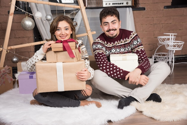お祝いの銀のボールの近くにクリスマスプレゼントと一緒に座っている若い幸せなカップル。