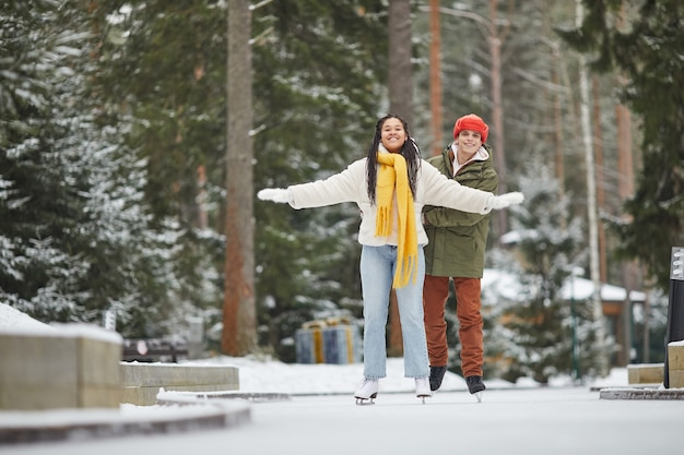 Young happy couple skating together outdoors and enjoying the winter holidays