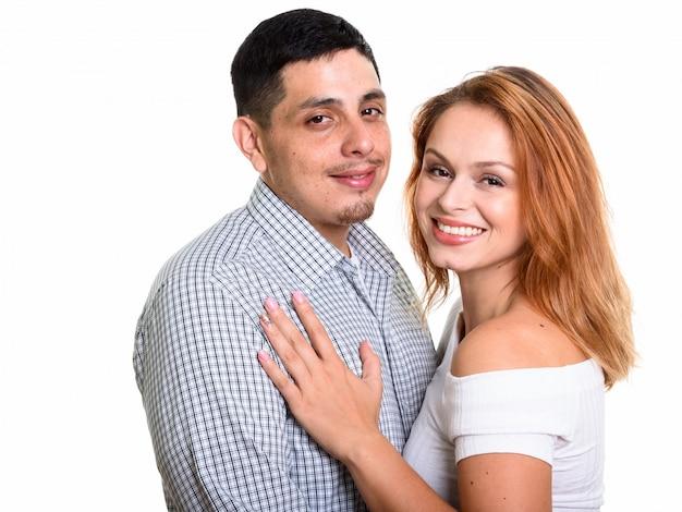 Молодая счастливая пара улыбается и обнимает друг друга в любви, изолированной на белом