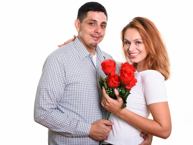 Молодая счастливая пара улыбается и влюбляется, держа красные розы и обнимая друг друга