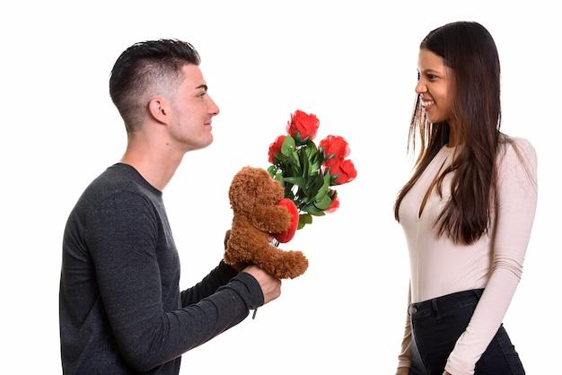 Молодая счастливая пара улыбается и влюблена в мужчину, дающего красные розы