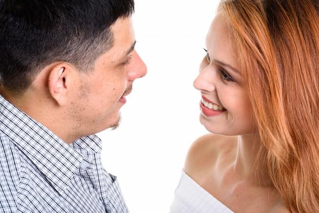 Молодая счастливая пара улыбается и смотрит друг на друга в любви, изолированной на белом