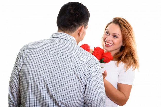 Young happy couple smiling and in love with man giving red roses isolated on white