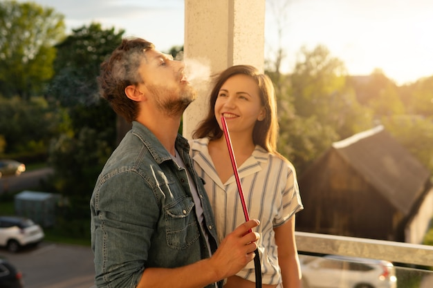 Молодая счастливая пара курит кальян на балконе