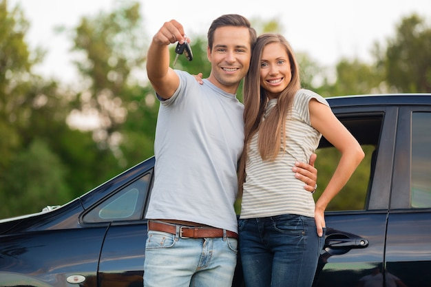 웃는 차 옆에 서 있는 젊은 행복한 커플 - 차 구매의 개념