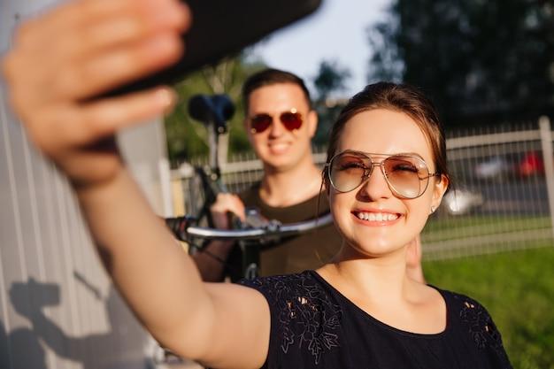 若い幸せなカップルはスマートフォンでselfieを取る、元気に笑みを浮かべて、バイクを保持している、サングラスをかけている男。サマータイム。