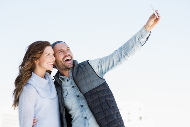 Young happy couple taking selfie on mobile phone outdoors