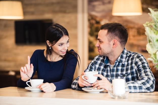 カフェで話している若い幸せなカップル
