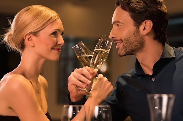 高級レストランでロマンチックなデートにシャンパングラスで乾杯する若い幸せなカップル。