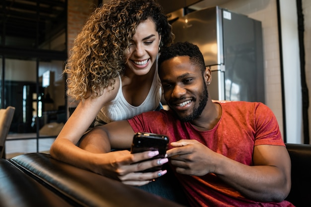 Young happy couple using a mobile phone together at home.