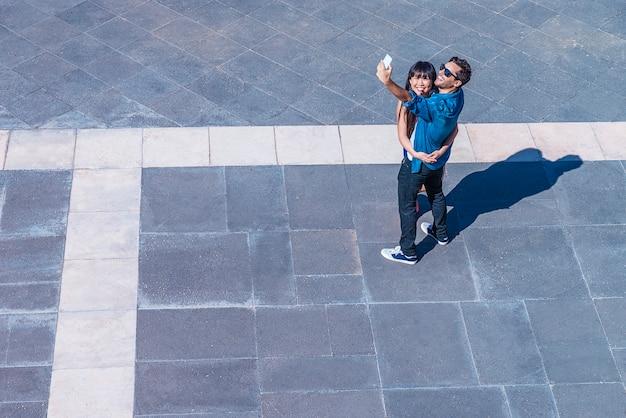 Молодая счастливая пара с помощью смартфона, сидя на улице. сделать селфи