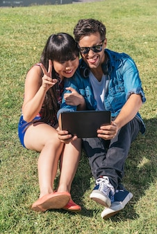 Молодая счастливая пара с помощью планшета, сидя в парке