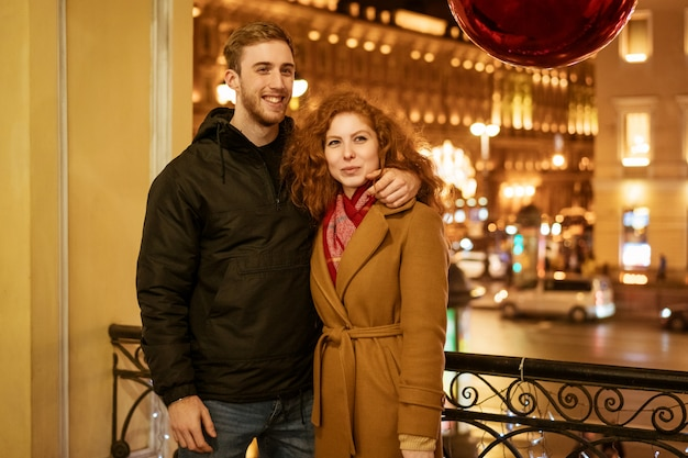 Молодая счастливая пара гуляет по городу вечером
