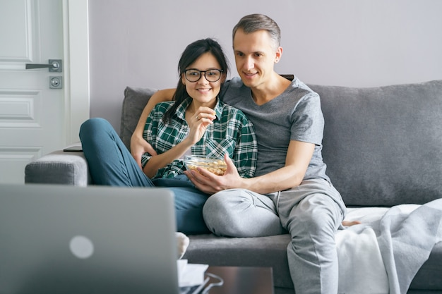 Young happy couple watching movie on laptop while sitting on sofa at home