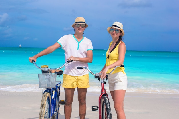 Young happy couple with bikes on white sandy beach