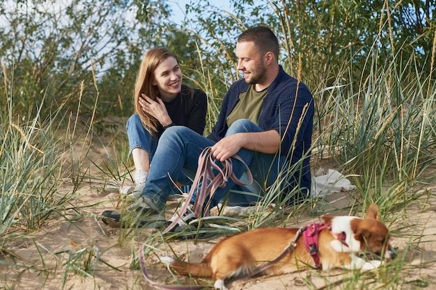 砂に座っているコーギー犬と若い幸せなカップル。ハンサムな男と美女