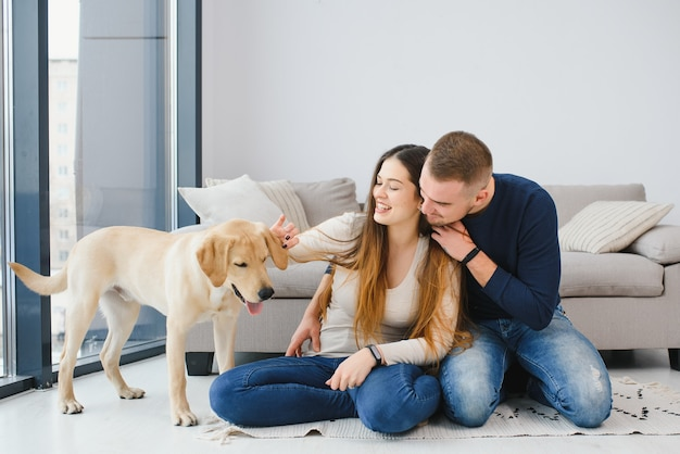 Молодая счастливая пара с собакой, сидя дома