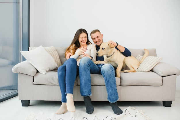 ソファに座っている犬と若い幸せなカップル