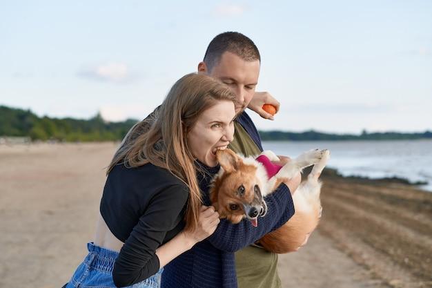 해변에 개 서와 젊은 행복 한 커플.