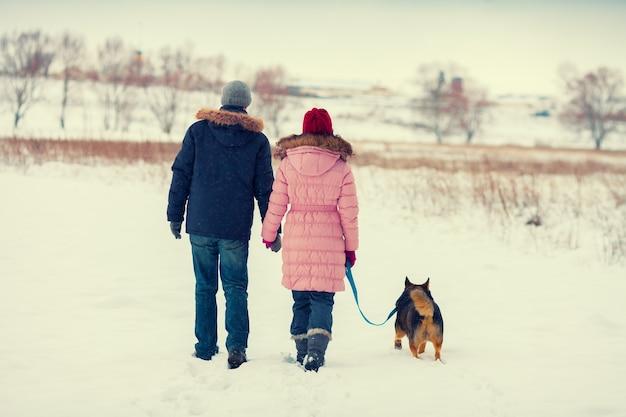 Молодая счастливая пара с собакой гуляет в заснеженном поле обратно к камере