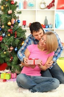 自宅のクリスマスツリーの近くに座っているプレゼントと若い幸せなカップル