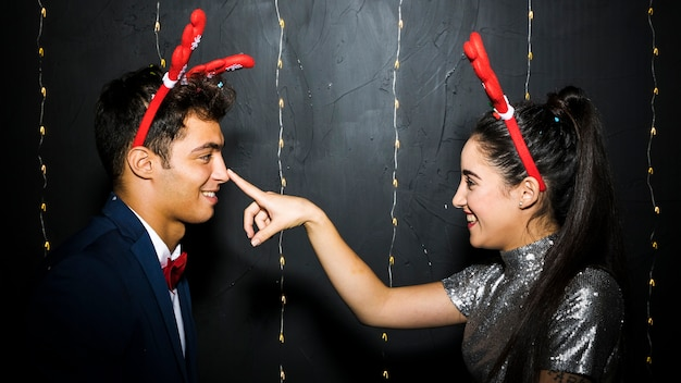 Young happy couple with red deer antlers headbands