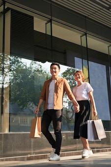 市内の買い物袋と若い幸せなカップル。