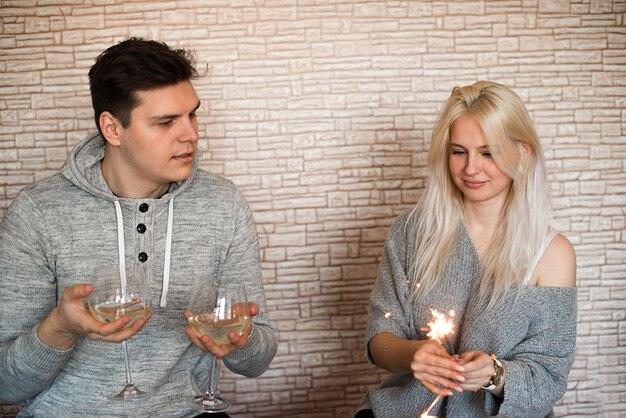 기념일을 축하하는 와인잔과 폭죽을 가진 젊은 행복한 커플