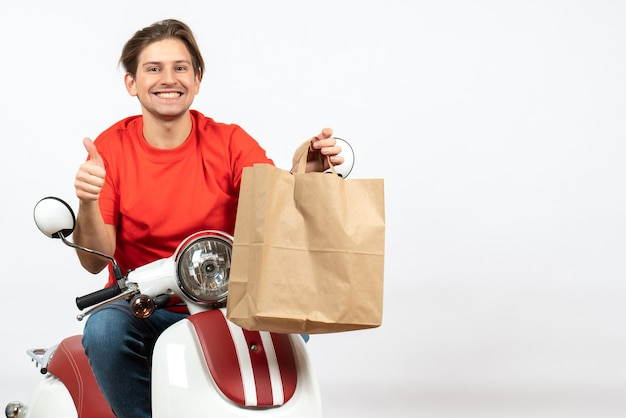 Young happy courier guy in red uniform sitting on scooter giving paper bag making ok gesture on white wall