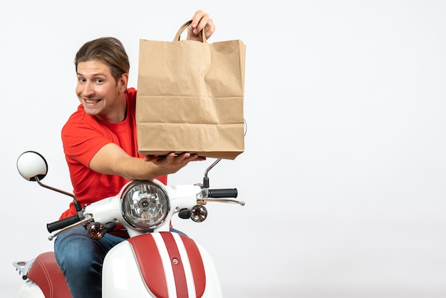 Young happy courier guy in red uniform sitting on scooter giving paper bag on white wall