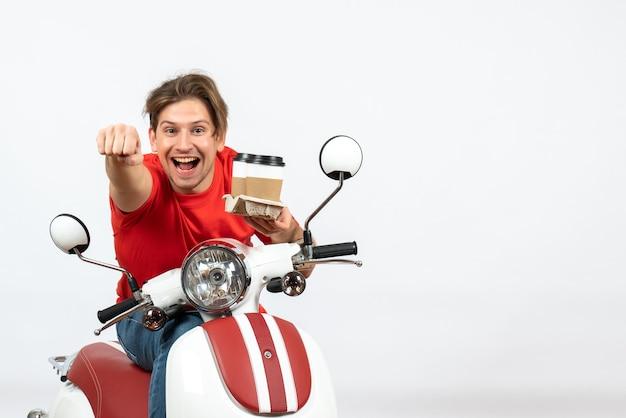黄色の壁に注文を保持しているスクーターに座っている赤い制服を着た若い幸せな宅配便の男
