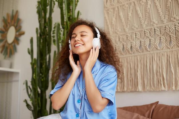 Giovane felice posa afroamericana riccia signora sul letto, ascoltando la canzone preferita in cuffia, ampiamente sorridendo e chiudendo gli occhi, godendosi la musica e la domenica mattina.