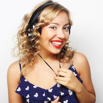 音楽を聴いてヘッドフォンで若い幸せな巻き毛の女性