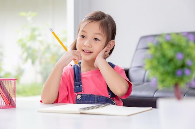 Молодая счастливая милая азиатская девушка наслаждается работать над ее сочинительством в ее домашней живущей комнате