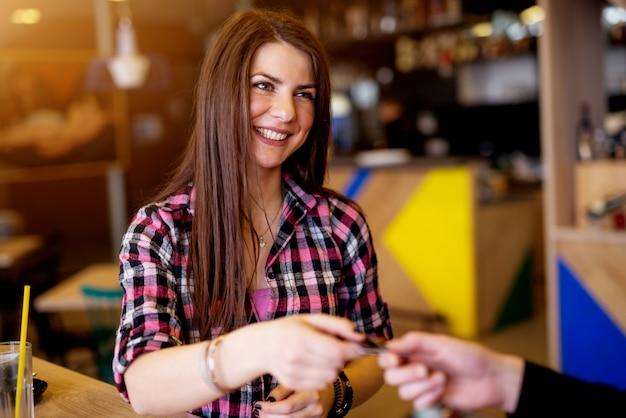 Молодая счастливая милая девушка использует ее банковскую карту для оплаты чека в кафе.