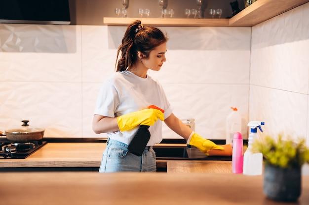Молодая счастливая милая женщина в желтых перчатках чистит свою кухню дома с моющими средствами.