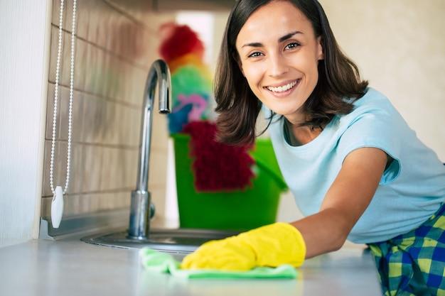 黄色い手袋をはめて若い幸せなかわいい女性が自宅のキッチンを掃除しています