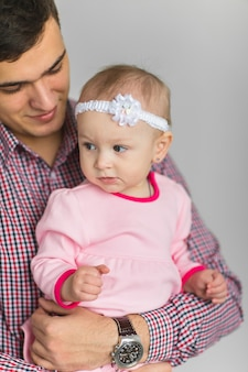Young happy dad keeps daughter