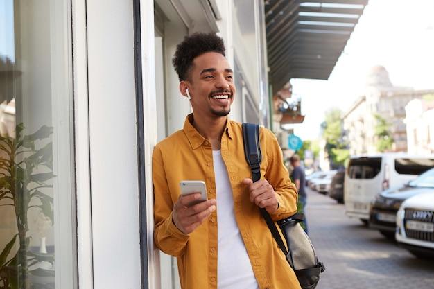Giovane uomo dalla pelle scura felice in camicia gialla, cammina per strada e tiene il telefono, ha ricevuto un messaggio carino dalla sua ragazza, distoglie lo sguardo e sorride ampiamente.