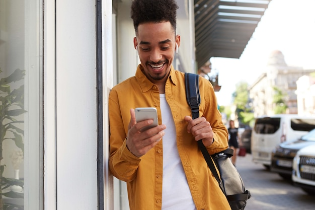 Young happy dark skinned man in yellow shirt, walking down the street and holds telephone, got a message with a funny video, looks joyful and broadly smiling.