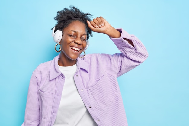 Young happy dark skinned woman enjoys favorite playlist in wireless headphones