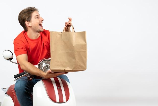 흰 벽에 종이 가방을 들고 스쿠터에 앉아 빨간 제복을 입은 젊은 행복 배달원