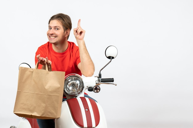 Young happy delivery guy in red uniform sitting on scooter holding paper bag pointing up on white wall