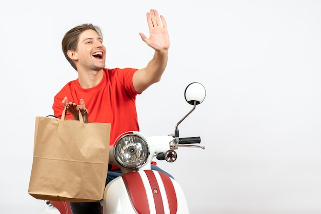 Young happy delivery guy in red uniform sitting on scooter holding paper bag and showing five on white wall