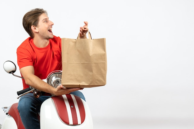 Young happy delivery guy in red uniform sitting on scooter holding paper bag on white wall