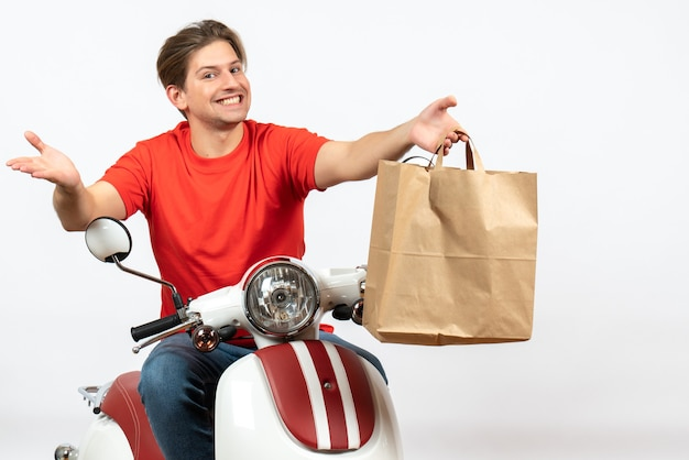 Young happy delivery guy in red uniform standing near scooter giving paper bag to someone on white wall