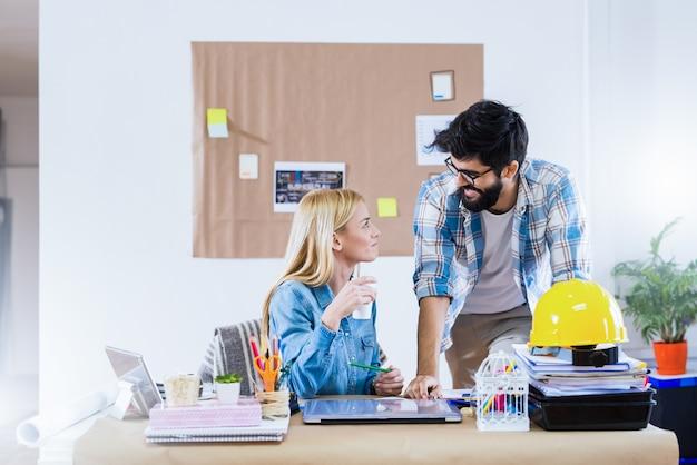 彼らのオフィスでビジネスについて話している若い幸せなデザイナー。