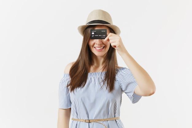 파란 드레스를 입은 젊은 행복한 우아한 여성, 흰색 배경에 격리된 신용 카드로 눈을 덮고 있는 긴 갈색 머리를 한 모자. 사람들의 라이프 스타일 뱅킹 개념입니다. 광고 영역입니다. 공간을 복사합니다.