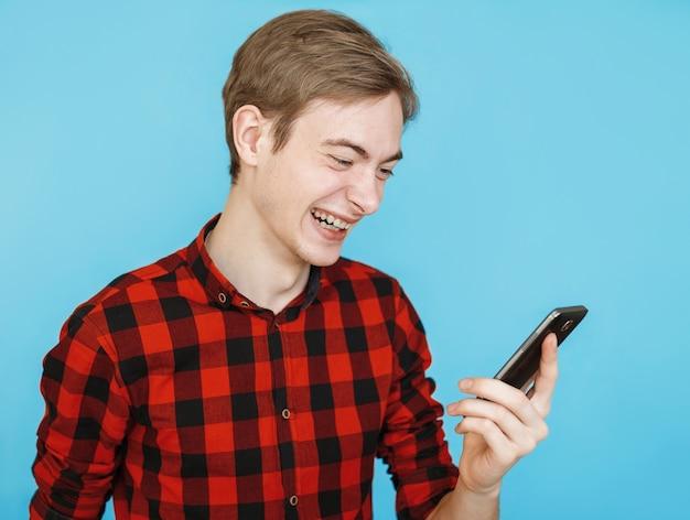 Молодой счастливый эмоциональный мужчина-подросток в красной рубашке на синем смотрит в смартфон